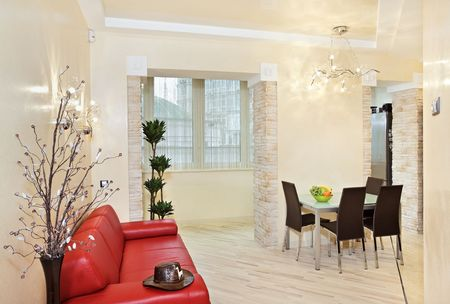 interior decor: Modern studio interior in warm tones with red sofa Stock Photo