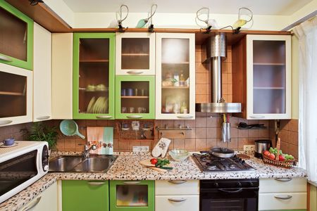 front view: Green Kitchen interior with many utensils