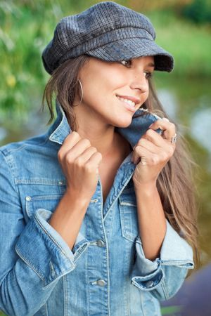 Attractive young woman dressed in jean and beret holding on herself jacket collar Stock Photo
