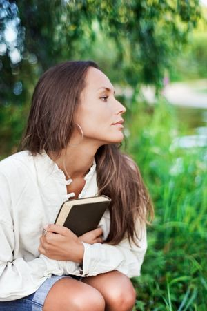 Thoughtful Young lady with book near the river in half face view photo