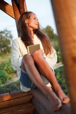 tuinhuis: Jonge vrouw met een boek in het verleden op de zons ondergang