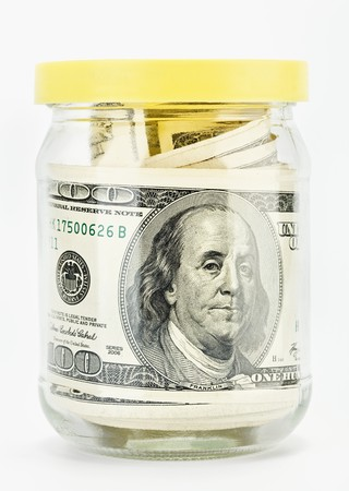 meanness: Many 100 US dollars bank notes in a glass jar isolated  on white background