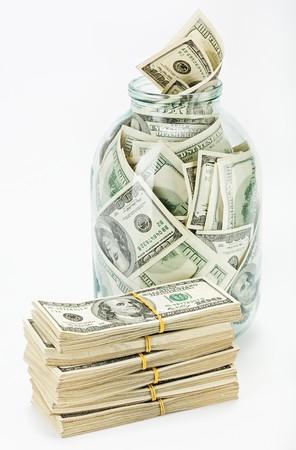 jarra: Muchos billetes de 100 d�lares de los Estados Unidos en un frasco de vidrio y paquete aislados sobre fondo blanco