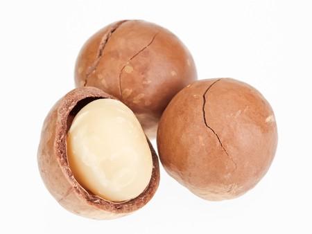 macadamia: Bombard�e et noix de macadamia en coque isol� sur fond blanc