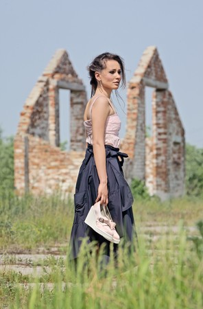 Attractive lady with shoes in her hand in half-turn view in front of brick ruins photo