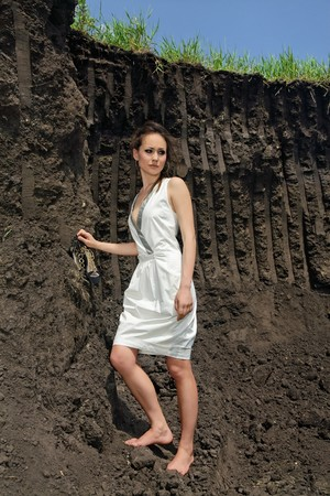 Beautiful brunette in white sundress inside a deep black ground quarry photo