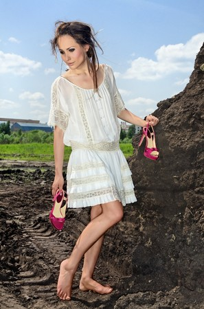 uncombed: Nice-looking lady in white standing barefoot with red heeled shoes in her hands