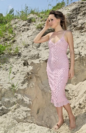 uncombed: Beautiful young woman standing barefoot in sand quarry in a pink sundress