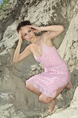 sand quarry: Beautiful young woman sitting barefoot in sand quarry in a pink sundress