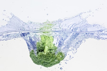 fluidity: Green broccoli falling in water on white with air bubbles