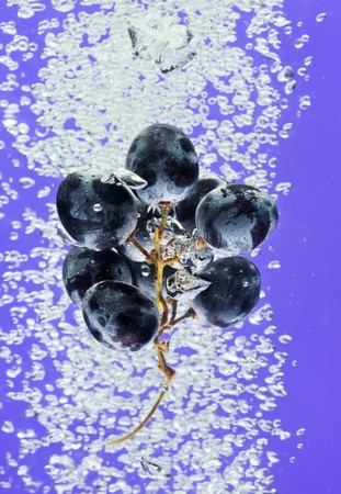 bleb: Bunch of grapes floating in blue water with air bubbles Stock Photo