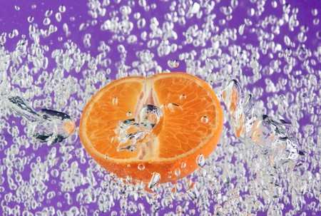 Orange (mandarin) floating in purple water with air bubbles photo