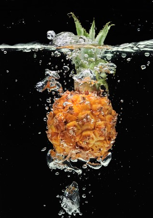 fruit and veg: Small pineapple falling in water on black with air bubbles Stock Photo