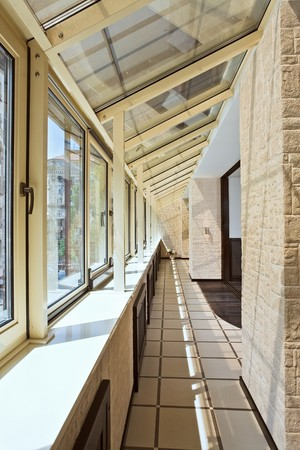 balcony window: Long balcony (gallery) interior with pvc windows Stock Photo