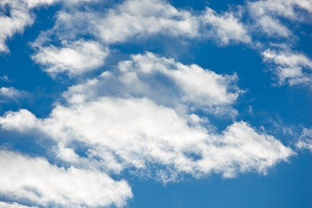 Fleecy clouds on blue sky background photo