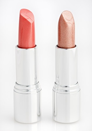 Two red and brown lipsticks isolated over white photo