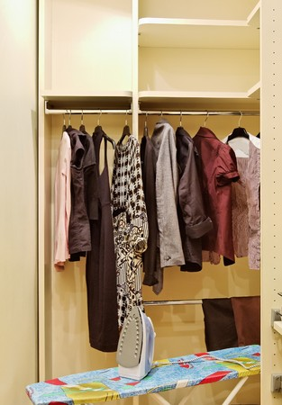 checkroom: Wardrobe with clothes and ironing board Stock Photo