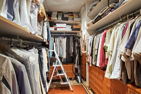 cloakroom: Wardrobe with many clothes and step-ladder Stock Photo
