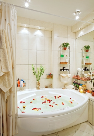 Modern bathroom in warm tones with jacuzzi and rose petals wide angle view photo