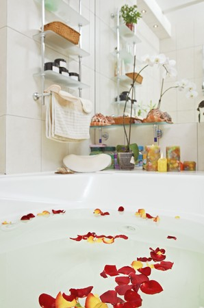 Part of bathroom with rose petals floating in water photo