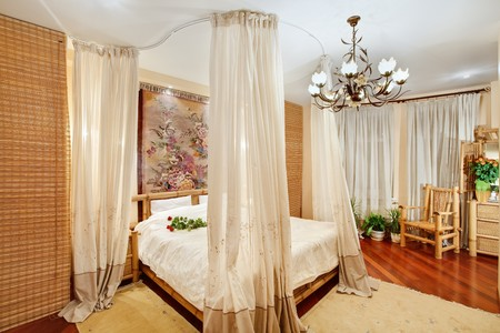 Medieval style bedroom with canopy bed on wide angle view photo