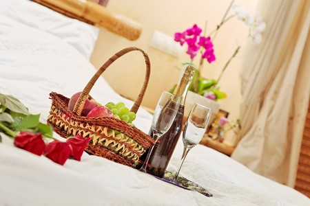 Roses, fruits basket and wine glasses on tea-tray in the bed Stock Photo - 7409353