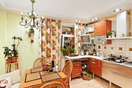 Kitchen interior with wooden furniture, table and many utensils in warm tones on wide angle view Stock Photo - 7441483