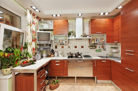 Kitchen interior with wooden furniture and many utensils in warm tones on wide angle view photo