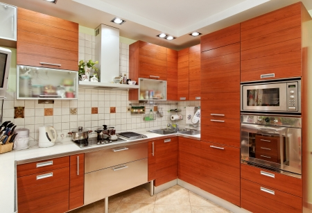 Kitchen interior with wooden furniture and many utensils in warm tones on wide angle view Stock Photo