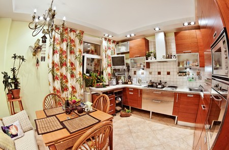 Kitchen interior with wooden furniture, table and many utensils in warm tones on wide angle view Stock Photo - 7441491
