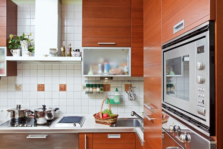 build in: Part of Kitchen interior with wooden furniture and build in microwave oven