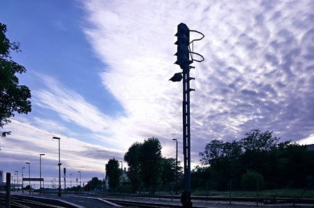 Semaphore on railway station in front of dramatic fleecy clouds sky photo