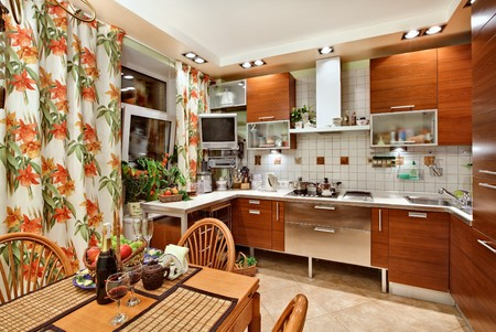 Kitchen inter with wooden furniture, table and many utensils in warm tones on wide angle view Stock Photo - 7478647