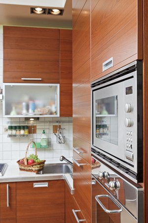 Part of Kitchen interior with wooden furniture and build in microwave oven photo