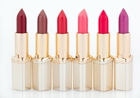 Multicolored color lipsticks arranged in line isolated on white photo