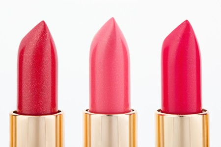 Three color lipsticks arranged in line isolated on white, macro photo
