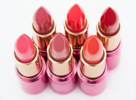 Multicolored color lipsticks arranged in two lines isolated on white, top view, shallow depth of field photo
