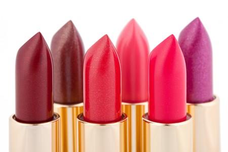 lapiz labial: Barras de labios de color multicolores dispuestas en dos l�neas aisladas en la profundidad del blanca, poca profundidad de campo  Foto de archivo