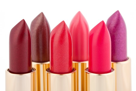 bright lipstick: Multicolored color lipsticks arranged in two lines isolated on white, shallow depth of field