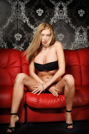Sexy young blonde lady in black lingerie on red sofa Stock Photo - 7610427