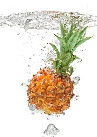 Small pineapple falling in water on white with air bubbles photo