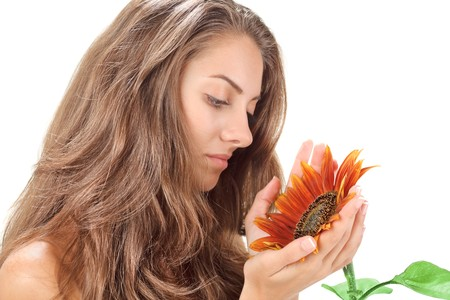 Young beautiful woman with long hairs holding sunflower near face photo