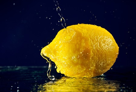 Whole lemon with stopped motion water drops on deep blue Stock Photo - 8004255