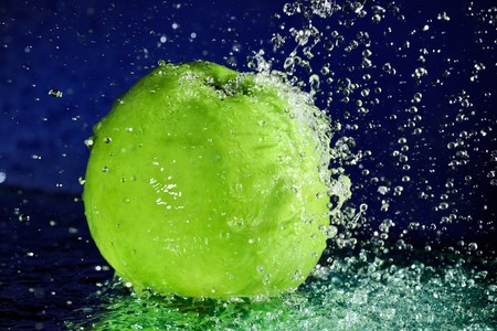 Whole green apple with stopped motion water drops on deep blue Stock Photo - 8004269