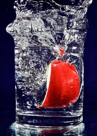 Slice of red apple falling down in glass with water on deep blue photo