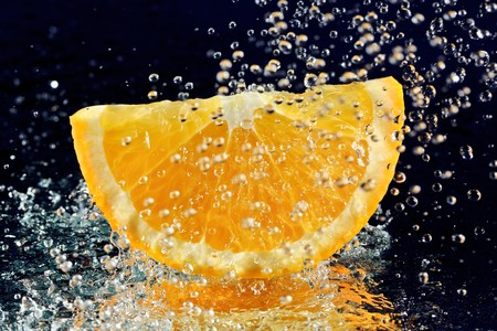 Slice of orange with stopped motion water drops on deep blue photo