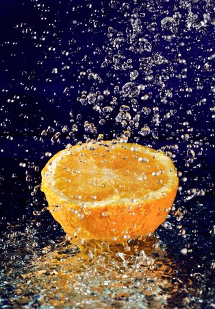 Half of orange with stopped motion water drops on deep blue Stock Photo - 8004270