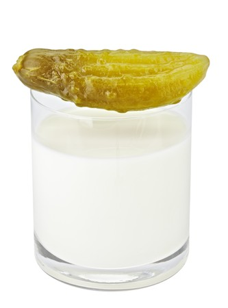 insipid: Incompatible eating products milk and salted cucumber Stock Photo