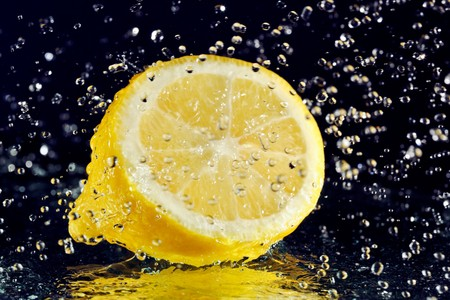 Half of lemon with stopped motion water drops on black Stock Photo - 8004286