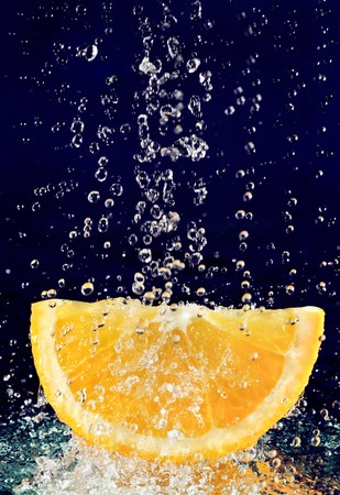 Slice of orange with stopped motion water drops on deep blue Stock Photo - 8004285